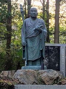 Статуя Эннина, важного ученика Сайчо, на фоне голубого неба, обращенная вправо.