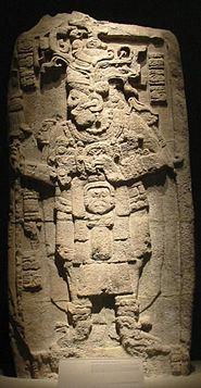 Рельефная скульптура, изображающая богато одетую человеческую фигуру, обращенную налево, со слегка расставленными ногами.  Руки согнуты в локтях, руки подняты на уровень груди.  Короткие вертикальные столбцы иероглифов расположены по обе стороны от головы, еще один столбец находится внизу слева.