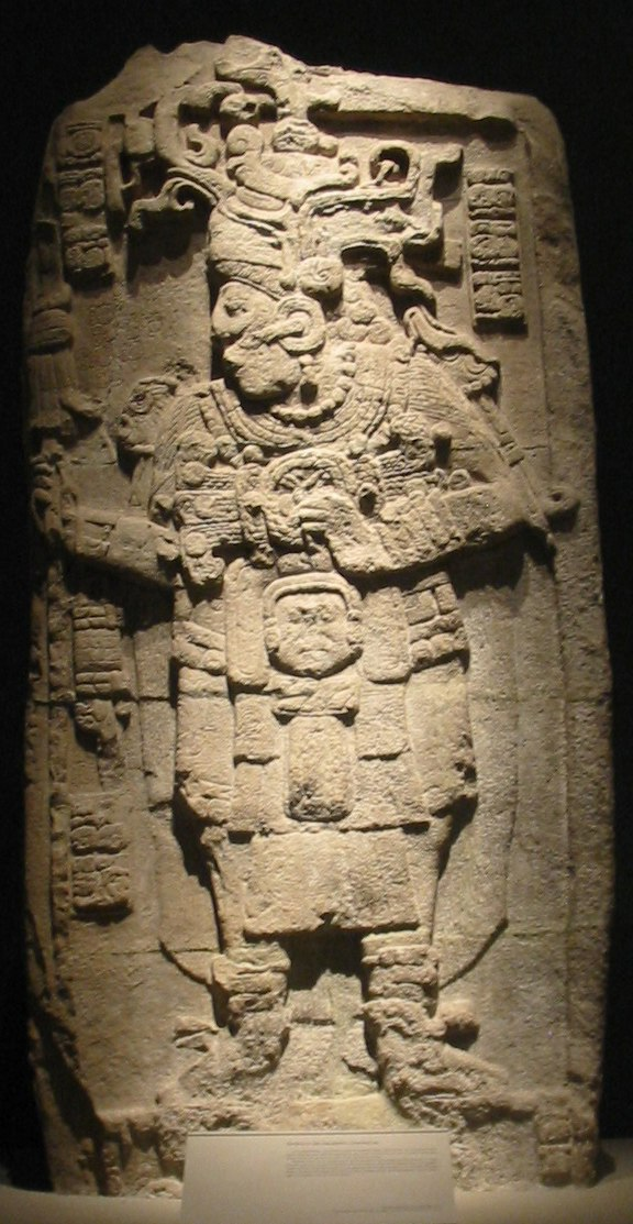 A relief sculpture showing a richly dressed human figure facing to the left with legs slightly spread. The arms are bent at the elbow with hands raised to chest height. Short vertical columns of hieroglyphs are positioned either side of the head, with another column at bottom left.