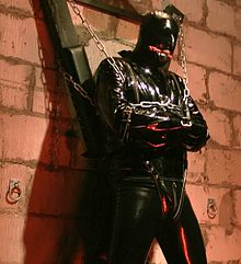 A bondage practitioner in a black PVC straight jacket chained to a St. Andrew's cross.