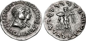 "Strato I - Coin of young Strato I and his mother Agathokleia. Obv: Conjugate busts of Strato and Agathokleia. Greek legend: BASILEOS SOTEROS STRATONOS KAI AGATOKLEIAS ""Of Saviour King Strato, and Agathokleia"". Rev: Athena throwing thunderbolt. Kharoshthi legend: MAHARAJASA TRATASARA DHARMIKASA STRATASA ""King Strato, Saviour and Just (=""of the Dharma"")""."