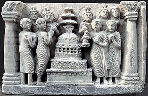 Circumambulation - Relief of ancient Indian Buddhists (monks at left, a lay couple at right, statues behind) circumambulating a stupa in a chaitya temple