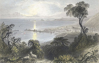 Swansea Bay - A view of showing Swansea bay and a town. Ships are sailing in the sea and a lighthouse can be seen in the background.