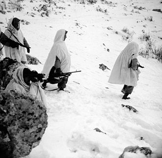 II Corps (Poland) - Snow camouflage coated AFPU cameraman, Sergeant Eric Deeming, filming troops of the 2nd Coy., 1st Battalion, 1st Carpathian Rifles Brigade, 3rd Carpathian Rifles Division, returning from a patrol. Height 1210, north of Rionero in Vulture.