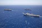 The amphibious assault ship USS Kearsarge (LHD 3), left, steams in formation with the amphibious dock landing ship USS Carter Hall (LSD 50), background, and the amphibious transport dock ship USS San Antonio 130616-N-SB587-1041.jpg