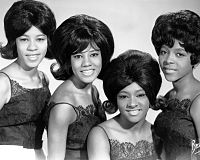A black-and-white photograph of four African-American woman smiling in the direction of a camera. They all have dark hair and are wearing dark-colored tops.