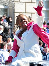 A woman is sitting and waving her hands. She is in her early sixties and wears a white suit and a pink scarf.