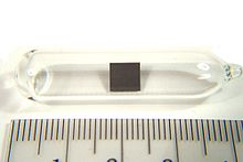 Small (3 cm) ampule with a tiny (5 mm) square of metal in it