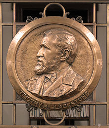 a circular bronze plaque has a raised impression of the bust of a man who is facing to the left.  The place is located on bronze railings.