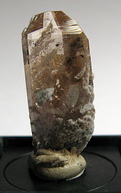 A terminated raw, golden topaz crystal.