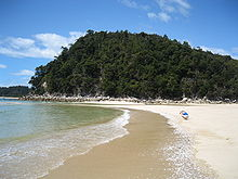 Photo showing clear blue water, a photographer or tourist capturing the water on a golden sanded beach and forested hills