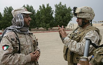 Bubiyan Island - First Sergeant Felix Acosta, weapons company 1st Sgt., speaks with a Kuwaiti soldier guarding an entrance to Bubiyan Island Nov. 21, 2009, where Marines and Sailors with the 11th Marine Expeditionary Unit practiced moving from ship to shore on landing crafts Nov. 20-24.