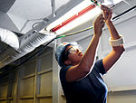 USS Carl Vinson sailor tightens fixture 120925-N-AU127-066.jpg