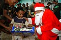 US Navy 041216-M-1188A-001 A boy smiles as he receives a gift from Santa Claus during the last day of operations for Joint Task Force Five Three Five (JTF-535) in the Philippines.jpg