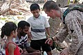 US Navy 050110-M-0764W-010 Hospital Corpsman Daniel Keenan, assigned to Marine Expeditionary Unit Service Support Group Fifteen, speaks with a Sri Lankan family about medical issues in the village of Colombo, Sri Lanka.jpg