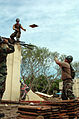 US Navy 050116-M-3295H-014 Engineering Aide 3rd Class Andrew K. Ebersonan assigned to Naval Mobile Construction Battalion Seven (NMCB-7), throws salvaged roofing tiles to Builder 1st Class Richard L. Gravener.jpg