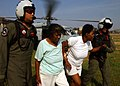 US Navy 050902-N-0535P-266 Navy Search and Rescue (SAR) Swimmer Aviation Warfare Systems Operators 1st Class Tim Hawkins and Scott Chun lead Hurricane Katrina victims to an evacuation center in New Orleans.jpg