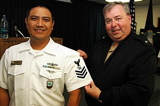 Terry McCreary - Rear admiral Terry McCreary presenting a rating insignia of a Mass Communication Specialist First Class (MC1).