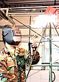 US Navy 080102-N-8547M-004 Steelworker 3rd Class Phillip J. Tremiti, assigned to Naval Mobile Construction Battalion (NMCB) 5, welds together a traditional.jpg