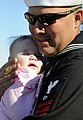 US Navy 081203-N-5345W-075 Fire Controlman 1st Class Chris Morge holds his daughter for the first time during a homecoming celebration at Naval Station Norfolk.jpg