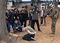 US Navy 090309-N-9573A-011 Cpl. Ian MacDonald, from the Fleet Anti-terrorism Security Team Pacific (FASTPAC), holds a simulated aggressor who broke through the perimeter breech of the base fence line as Republic of Korea media.jpg