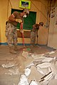 US Navy 090404-N-1057H-058 eabees assigned to Naval Mobile Construction Battalion (NMCB) 11, Detachment Horn of Africa sweep debris at the Ecole Ali Sabieh Primary School.jpg
