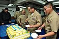 US Navy 110401-N-SF508-346 Chief Culinary Specialist Cruz Ayala, center, from Caguas, Puerto Rico, serves the cake during the 118th chief petty of.jpg