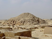 A photograph of the ruined pyramid of Unas. Parts of the base of the pyramid remain generally intact, with visible polished stone blocks, while the head of the pyramid resembles a large mound of sand. The ruins of the mortuary temple can be seen in the foreground. Segments of the bases of the walls of the mortuary temple and pyramid complex have been retained, though much of the structure is in ruins.
