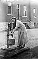 Unidentified woman using a water pump in a South St. Louis neighborhood.jpg