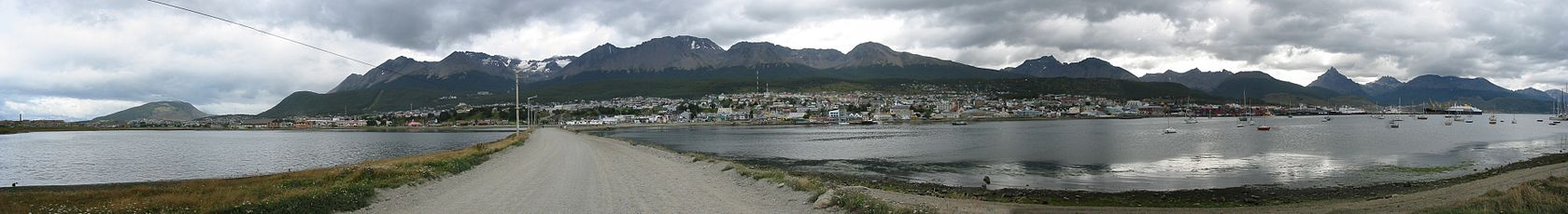 A small city across a gray waterway under lowering gray clouds. A road leads to the city across a causeway. Mountains with snow and a low treeline form the backdrop. A few boats are in the water.