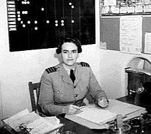 Dark-haired woman in light-coloured military uniform sitting behind a desk