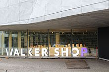 Window of a modern store, large lighted letters spelling Walker Shop in white, with the P in purple