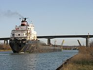 A ship traversing the Welland Canal, with the Garden City Skyway in the background.