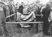 The pushcart or wheelbarrow where Nellie Kehoe's dead body was found (covered by a cloth and surrounded by onlookers) and protected with a crude fence