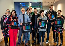 a group of people posing for the camera, each holding a Wikidata-branded bag