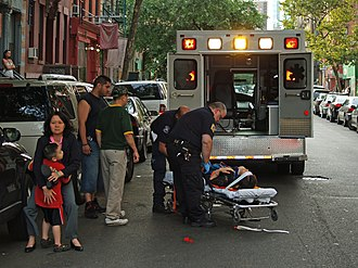 Emergency - An emergency medical technician treats a woman who has collapsed in the street in New York. Dangers to life and health are serious enough that emergency response systems are considered vital.
