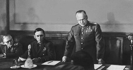 Marshal Georgy Zhukov reading the German capitulation in Berlin. Seated on his right is Air Chief Marshal Sir Arthur Tedder. Zhukov reads capitulation act.jpg
