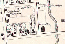 An old map showing a block of streets with lot lines and solid black rectangles representing buildings with their owners' names next to them. There is a river at the right