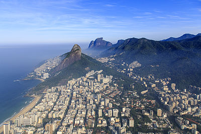 An aerial view of Leblon, capturing the beach, Dois Irmãos, Pedra da Gávea, and the Vidigal and Rocinha favelas