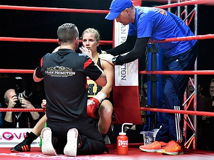 Female boxer Tina Rupprecht receiving instructions from her trainer while being treated by her cutman in the ring corner between rounds. 2017-12-02 Tina Rupprecht - Anne Sophie Da Costa - DSC2771.jpg