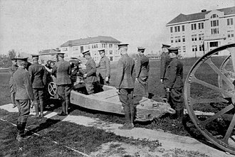 Utah State University - Military personnel with 8-inch howitzer drill on the Quad. (Year: 1922 or earlier)