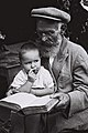 "A DUTCH CONVERT TO JUDAISM WITH HIS GRANDCHILD IN HIS LAP, STUDYING THE BIBLE ON HIS FARM IN ""NAHALAT YITZHAK"" TEL AVIV. הולנדי שהתגייר קורא יחד עם נכD836-063.jpg"