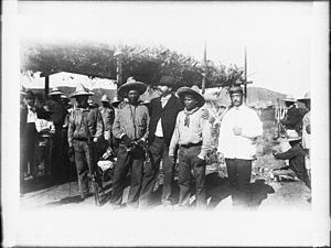 Yaqui Wars - a group of Yaqui Indians at the surrender and signing of peace treaty at Ortiz, Mexico, ca.1910. Two Mexicans stand near three Indians in the foreground.