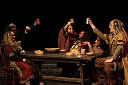 Actors in klingon costumes raise cups on table.jpg