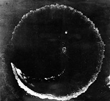 Photograph looking directly down at the ocean's surface from a high altitude. There is a rough circle on the surface that is about as wide as the photograph. The top deck of a ship is seen at the lower left of the circle; the length of the ship is much smaller than the circumference of the circle.