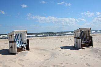 Strandkorb chairs on Usedom Island, Germany. Not only does the service sector grow because of tourism, but also local manufacturers (like those producing the strandkorb chairs), retailers, the real-estate sector and the general image of a location can benefit. Ahlbeck Strandkorbe 2013.JPG