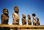 Row of six large stone statues with elongated heads on a grassy slope