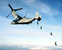Four U.S. Marine paratroopers jump from the rear loading ramp of an MV-22 Osprey