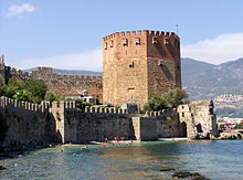 A eight-sided medieval tower built of red and yellow brick rises above a green sea in which swimmers play.  Stone walls run along the shore and further up from the tower.