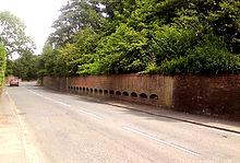 Foto de muro kun 17 duonrondaj kradoj konstruis en ĝi. La kradoj estas interspacigitaj horizontale laŭ la longo de la muro